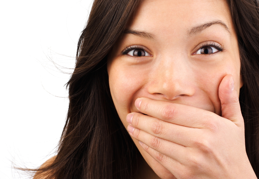 girl-covering-her-mouth-with-her-hand